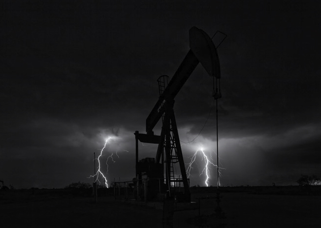 A lone pumpjack is flanked by twin lightning strikes at 3:36am during a rare October electrical storm near Denver City, Texas. By Robert D. Flaherty